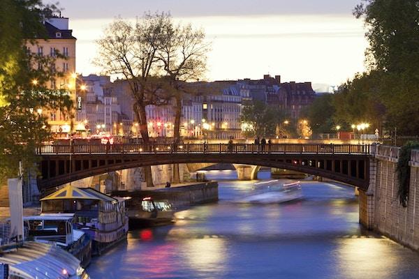 Seine River & Pont au Double nära Notre Dame Cathedral i skymningen, Paris, Frankrike