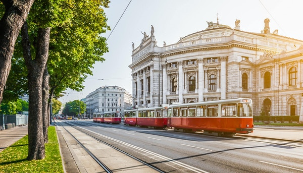 Famous Wiener Ringstrasse with historic Burgtheater (Imperial Court Theatre) and traditional red electric tram at sunrise with retro vintage Instagram style filter effect in Vienna, Austria.