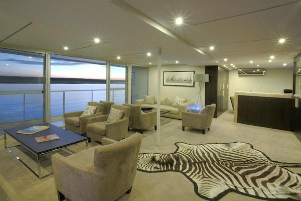 Ship lounge med sebra matta på golvet, bord, stora panoramafönster. Foto.