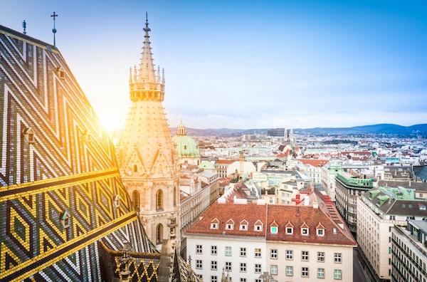 Flygfoto över hustakarna i Wien från norra tornet i Stefansdomen inklusive katedralens berömda utsmyckade, rikt färgade tak skapat av 230 000 glaserade brickor, Österrike