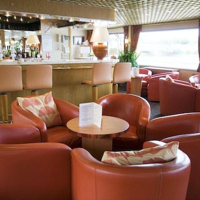 Röda fåtöljer i loungen ombord på MS Rhone Princess