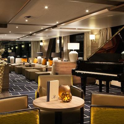 Bar med stolar och piano på flodkryssningsfartyg