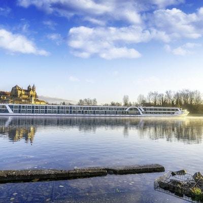 Flodkryssningsfartyg på floden mot slott i morgonstemning