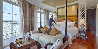 Svit med trägolv, dubbelsäng, stol, bord, stora fönster och en som rengör sängen. Foto.
