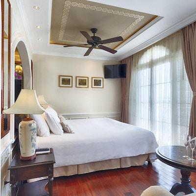 Svit med trägolv, dubbelsäng, soffa, lampor, takfläkt och stora fönster. Foto.