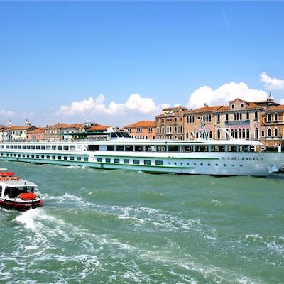 Kryssningsbåten MS Michelangelo ligger i hamnen med gamla byggnader i bakgrunden