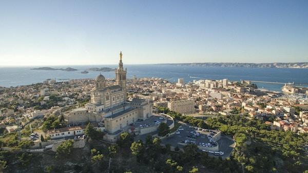 Sikt med hög vinkel av stadsbilden vid havet. Notre Dame de la Garde i Marseille mot klar himmel. Byggnader vid seascape på solig dag.