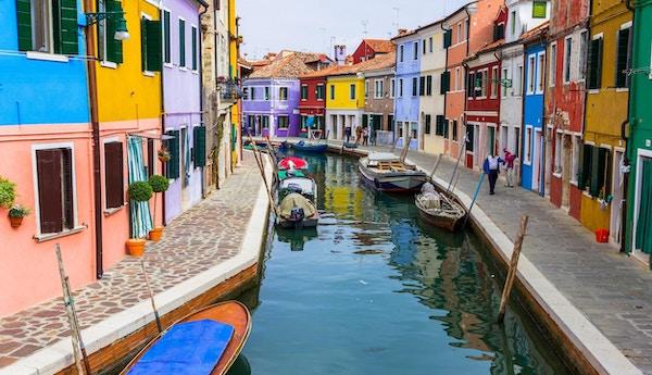 Burano kanal full av båtar och färgglada hus
