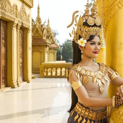 En traditionell kambodjansk apsara dansare överväger utsikten över templets innergård.