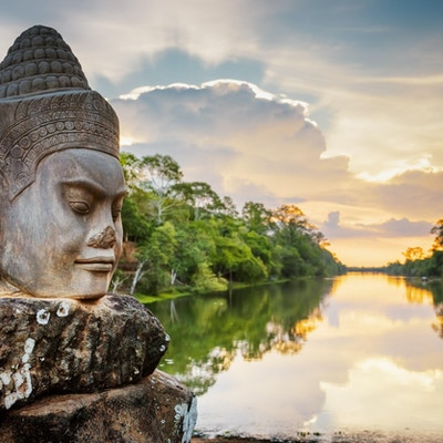 Stenframsida Asura på gångväg nära South Gate of Angkor Thom i Siem Reap, Kambodja. Härlig solnedgång över forntida vallgrav i bakgrund. Mystiska Angkor Thom är en populär turistattraktion.