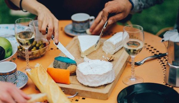 Tappning tonas upp närbilden av tabellen i trädgården i ett Paris förortshem, fylld med traditionell fransk mat, olika typer av ost, vin, hemgjord bagettbröd och frukt och grönsaker. Vänner njuter av det trevliga vårvädret, har en typisk fransk brunch, med vin, brieost, ädelost och baguetter.