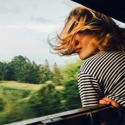 Kaukasisk kvinna som ser sikten från tågfönstret