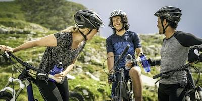Foto av en familj som har roligt och ler medan man tar en vattenpaus i bergen under en cykeltur.