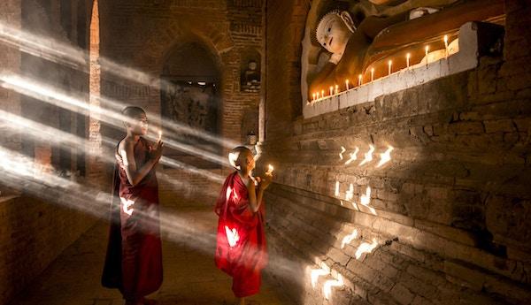 Två unga buddhistiska munkar som ber inne i templet i Bagan, Myanmar