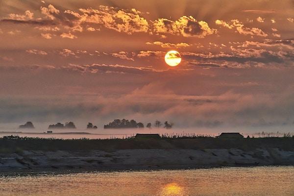 Sandbank med hus och träd i dimma och solnedgång längs floden. Foto.