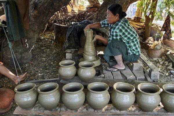 Kvinna som squatting i traditionella kläder som gör lägerburkar Foto.