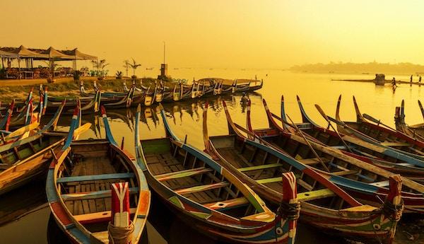Soluppgång på U Bein-bron med båten, Mandalay, Myanmar