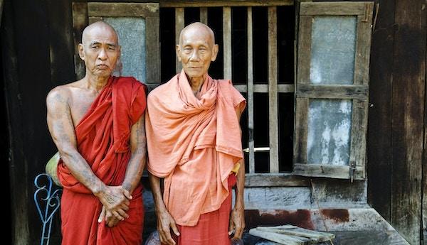 Två burmesiska munkar i 70-talet står tillsammans på verandan till deras kloster i Mandalay, Myanmar