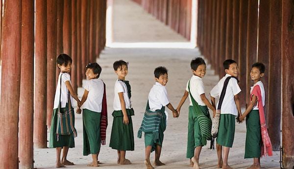 Sju små barn ler mot kameran när de är på väg till skolan