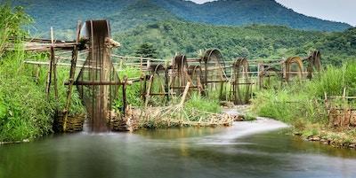 Bevattningssystem som består av trävattenhjul med flod och frodiga berg. Foto.