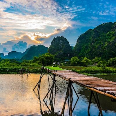 Vackert landskap med flod, träbrygga, himmel, gröna kullar och berg. Foto.