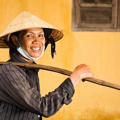 Le bärande frukt för kvinna med gult korn i bakgrunden. Foto.