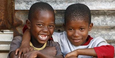 Två unga afrikanska pojkar som sitter framför deras ödmjuka bostad precis utanför Johannesburg, Sydafrika.