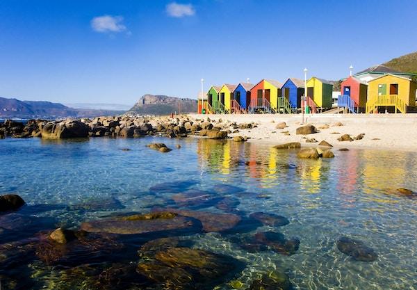 Kristallklart vatten från St James Beach och tidvattenpool med dess färgglada kojor, Kapstaden, Sydafrika