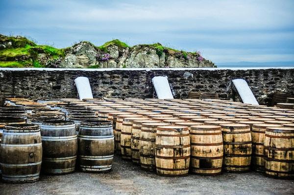 Whiskyfat vilar längs en vägg nära havet på Isle of Islay, Skottland, Storbritannien