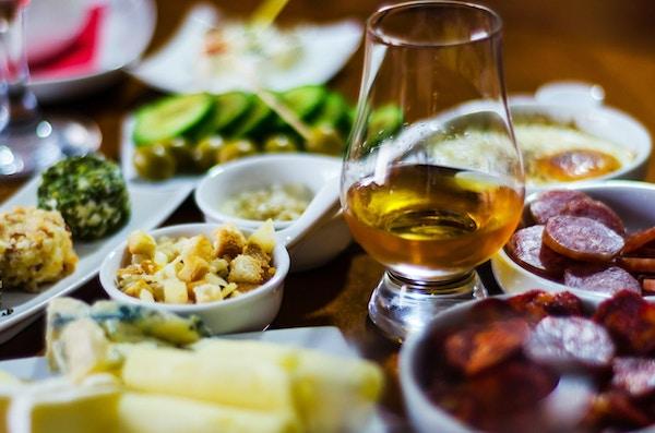 glas whisky single malt och med olika aptitretare i små portioner, läckra snacks och dryck
