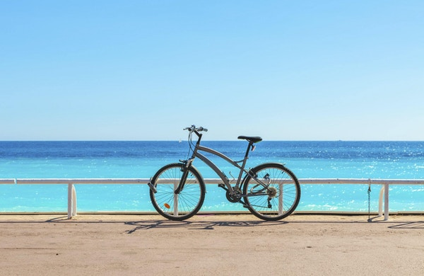 Cykla på den berömda Promenade des Anglais som Medelhavet på bakgrund i Nice, Frankrike.