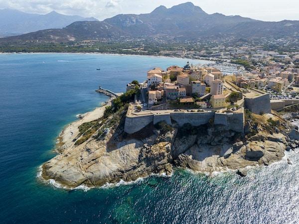 Flyg- sikt av den Calvi staden, Korsika, Frankrike. Väggar i staden, klippa med utsikt över havet