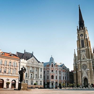 """""""Det centrala torget i Novi Sad, Serbien eller Trg Slobode. Synlig är traditionell arkitektur, parochial romersk-katolska kyrkan med namnet Marias och statyn av Svetozar Miletic. Se fler bilder som detta i:"""""""