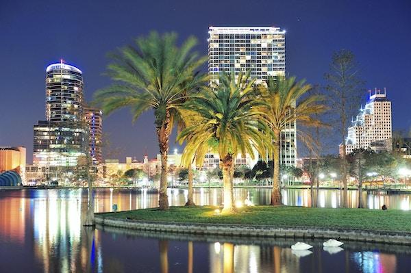 Orlando centrum horisont panorama över sjön Eola på natten med urbana skyskrapor, tropiska palmer och klar himmel.