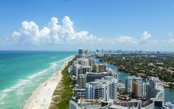 Ser ner South Beach i Miami. Full utsikt över stranden till vänster och staden till höger. Härlig blå himmel på en klar dag.