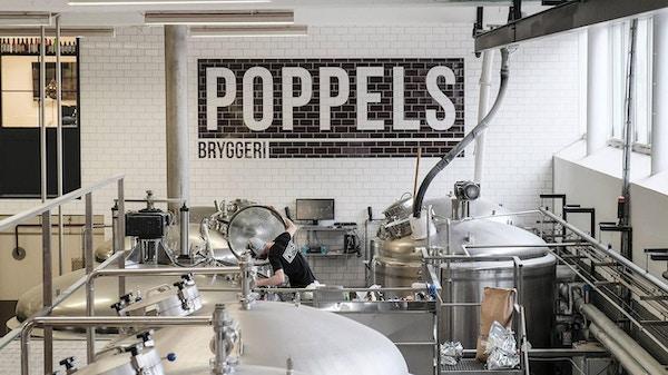 Bryggeriutrustning och stort Poppels logo på kakalvägg, Poppels Bryggeri, Göteborg, Sverige