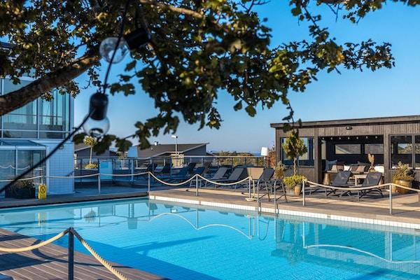 Utomhuspool med trädäck, séparée, lounge, solstolar, blå himmel och sol, Torekov Hotell, Båstad, Sverige