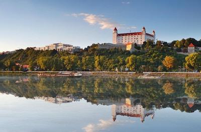 Bratislava slott med reflexion i floden Donau