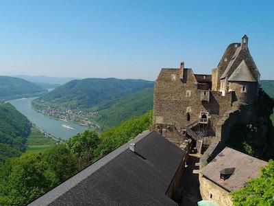 Panorama över floden och frodiga kullar med slottfördärvar i förgrunden.