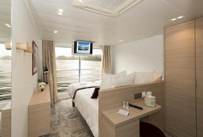 Stuga med matta, säng, garderob och fransk balkong. Foto.