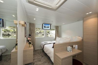 Stuga med säng, filt, skåp och små fönster på nedre däck. Foto.