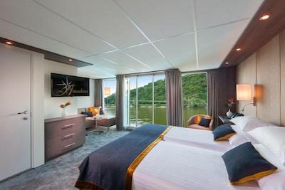 Säng mot panoramafönster på flodkryssningsfartyget