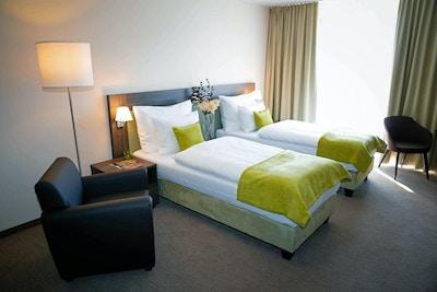 Hotellrum med två enkelsängar och en fåtölj