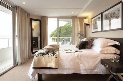 Stuga med dubbelsäng, kuddar, filtar, bilder på väggen och stora fönster. Foto.