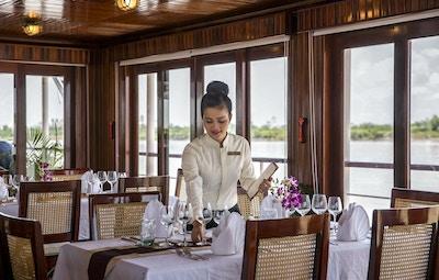 Flodkryssningsrestaurang med bord, stolar, siffror, glas, blommor och en dam som täcker bordet. Foto.