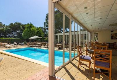 Restaurang med servering både inom- och utomhus, pool, gröna omgivningar, blå himmel och sol, Bluewater Hotel, Colonia Sant Jordi, Mallorca, Spanien