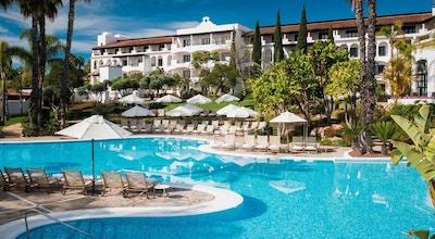 Pool med oregelbunden form, solstolar, parasoller, palmer, grönska, blå himmel och sol, The Westin La Quinta Golf Resort & Spa, Marbella, Spain
