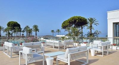 Uteservering på en av restaurangerna med utsikt över pool, palmer och hav, blå himmel och sol, Hotel Sol Marbella Estepona, Marbella, Spanien
