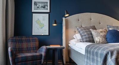 Blått rum med härlig heltäckningsmatta och fåtölj, Torekov Hotell, Båstad, Sverige