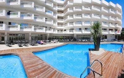 Poolområde med trädäck, palm, solstolar och hotellete med balkonger från rummen, Hotel Bernat II, Calella, Spanien
